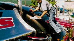 A TSS driver maintains his balance while polishing the raised roof of his sleeper.