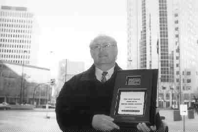 HIS OFFICE: Standing at Portage and Main, this Winnipeg city driver feels right at home. Ozouf explains he has racked up more than two million miles without a preventable accident.(Photo by John Curran)