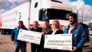 THANKS: Challenger's Dave Bennison, the Salvation Army's Neil Lewis, the OTA's David Bradley, the Red Cross' Tanya Elliot and Challenger's Beau Rose took part in the fleet group's official thank you ceremony. Both charitable groups took home $2,500 for helping truckers immediately after the Sept. 11 attacks.