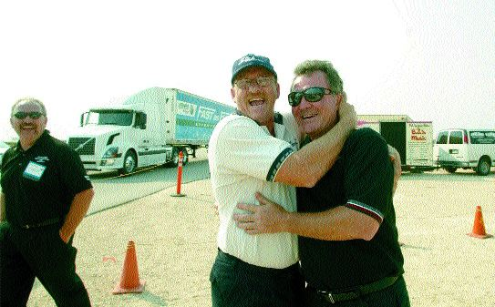 NATIONAL WINNER: Dwight Fisher, with SLH Transport, gives Peter Bergin - SLH Transport president a huge hug after competing in the Five-axle/Tandem Tandem Class category at the 2003 National Professional Truck Driving Championships held in Winnipeg Sept.6. Fisher was also the Grand Champion.