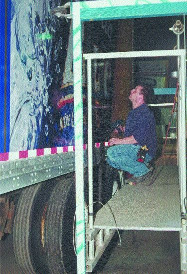 FLASHY: Mile Baric from Turbo Images works on installing graphics for Labatt Breweries' fleet of trailers. Photo by Katy de Vries
