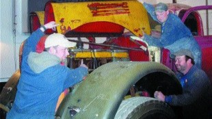 "CLASSIC: George Tackaberry might have the world's biggest collection of running and plated antique trucks and you can see many of them at the Athens Fair, Athens, Ont. July 16-18. Here Greg Tackaberry (left), Geoff Godkin (top) and Roger Simpson (right) are restoring a very rare 1949 International KB 14 Diesel, possibly the only one in existence. ""You're only as good as the people you have working for you,"" says owner George.Photo by Harry Rudolfs"