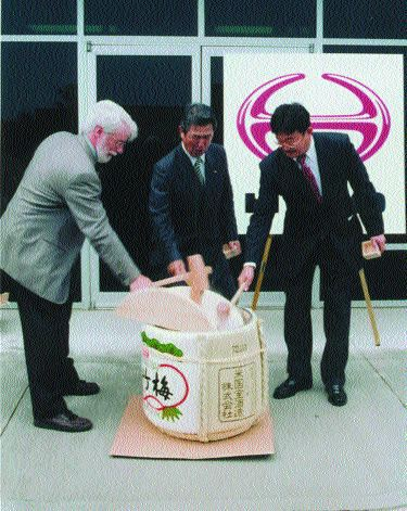 NEW DIGS: Hino officials broke open the sake to celebrate.