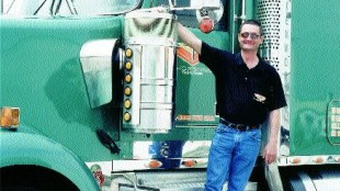 HAPPY CAMPER: Owner/operator Andy Brown (with his 2003 Kenworth) has been hauling for the Thorsons for 10 years now.  Photo by Ingrid Phaneuf