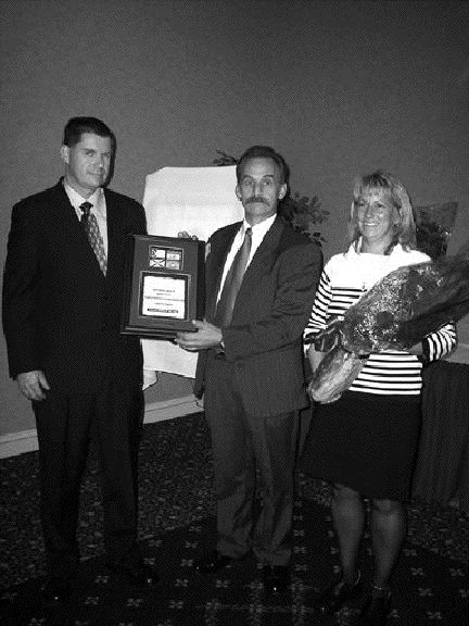 "Honoured: William Haslett (centre) was presented with the ""Driver of the Year Award"" by Ted Booth of Volvo Trucks Canada at the Atlantic Provinces Trucking Association's (APTA) annual conference. Also pictured is Haslett's wife, Nancy. Other winners at the APTA event included Garry Alderdice who won the ""Safety to Motor Transport Award,"" Ronald Groundwater who won the ""Good Samaritan Award,"" Christine Rankin who won the ""Dispatcher of the Year Award,"" and former APTA chairperson Lee Ann McConnell who won the ""Service to the Industry Award."""
