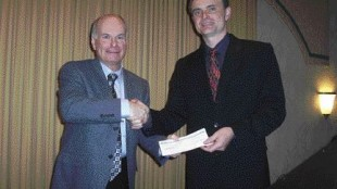 HELPING HAND: David Marshall of the Fraser Basin Council receives a check from B.C. Environment Minister Barry Penner for biodiesel outreach work.