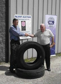 GOOD CAUSE: Stephen Fulton from Fulton Forwarders was the winning bidder on a set of Michelin tires. Terry Fulton (right) accepted the tires on his behalf. He's pictured with NAL president Gary Lindsay (left).