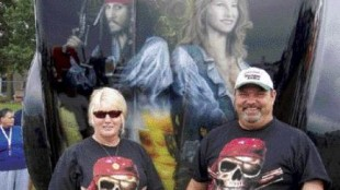 A COUPLE O' BUCKANEERS: Bob and Shelley Brinker show off the hood of their Classic XL Freightliner. Pictured alongside Johnny Depp's pirate character is their daughter Amie, who passed away last year.