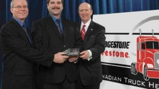 HAPPY HERO: Shawn Berube (centre) accepts the 50th Anniversary Bridgestone Firestone Canadian Truck Hero Award from David Scheklesky, Bridgestone Firestone Canada (left) and David Wilkins, US Ambassador to Canada.