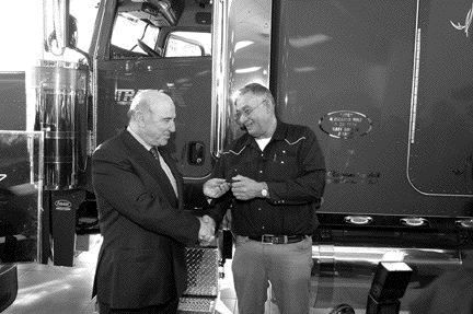 LOYALTY REWARD: TransX driver Joe Nayanokee accepts the keys to a new Pete from company president Louis Tolaini.