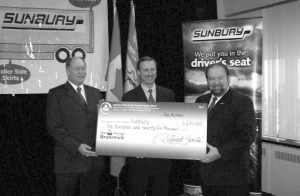 HELPING OUT: Minister of Environment Roland Mache (left) and Minister of Transportation Denis Landry (right) present Sunbury's vice-president of transportation, John Murphy, with a cheque for $675,000 to fund the installation of APUs in Sunbury's owner/operator fleet and the launch of a trailer skirt pilot program.
