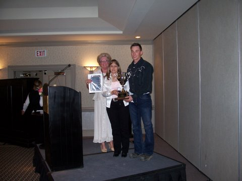 Marie Hibbard (left) presents the AMTA's safety award posthumously to John Tessier via his wife Chris and son Tyler at the AMTA convention in Banff.