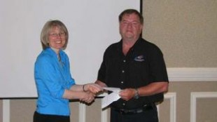 Bill Dowe, TANS vice-chair, presents Early Intervention's Brenda Putnam with a cheque on behalf of TANS.