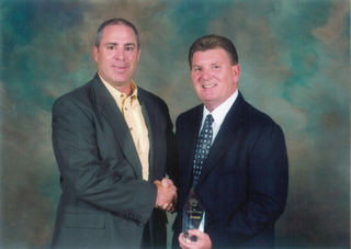 Doug Frank, general manager, logistics shared services, Schneider Logistics (left) presented the award to Jeff Lewis, manager, corporate accounts, TST Overland Express.