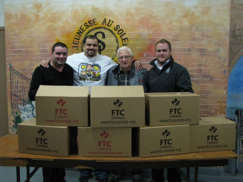 CFLer Marwan Hage (second from left), FTC Canada's Ryan Fletcher (far right) and staff from Sun Youth were on hand to distribute food boxes in Montreal last week. Keltic Transportation offered its services to help make deliveries during the event.
