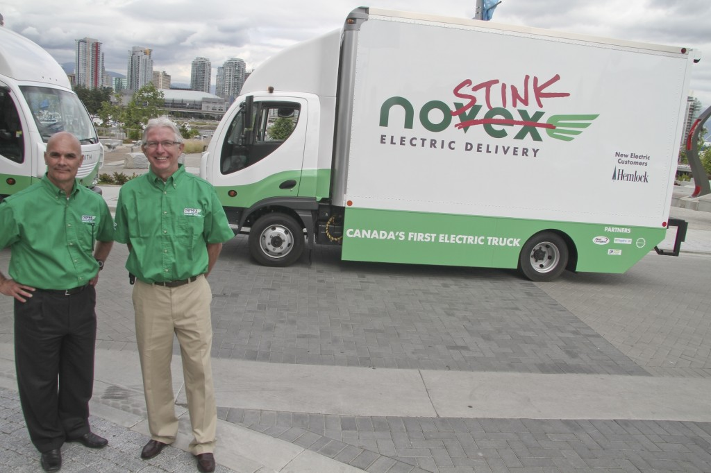 Novex CEO Rob Safrata (left) and president Ken Johnston pose in front of the company's two new 100% electric-powered trucks on June 24.