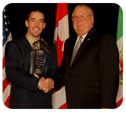 Inspector Richard Robinson, left, accepts his award from CVSA president Francis France.