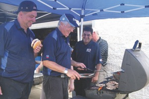 THANK YOU BBQ: Quick Truck Lube staff kept their burgers hot and their heads dry during the company's customer appreciation day July 9.
