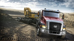 The new Cat CT660 pulls a piece of Caterpillar construction equipment.