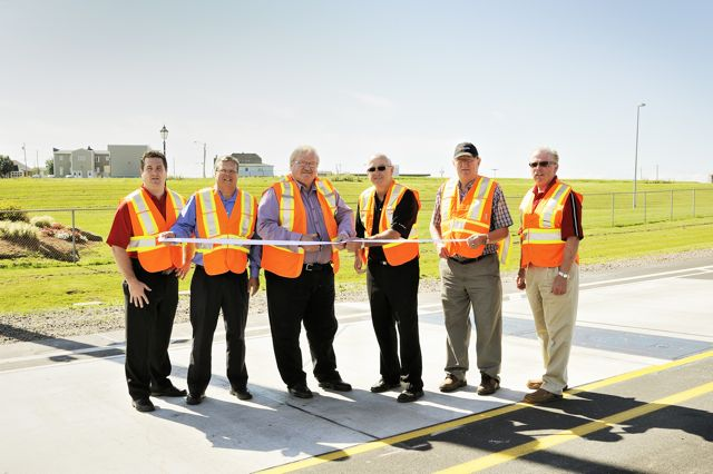 Minister of Transportation and Infrastructure Renewal Ron MacKinley and Minister of Agriculture George Webster are joined by (L-R): Tyson Kelly, director with the Atlantic Provinces Trucking Association; Michel LeChasseur, general manager of the Confederation Bridge; Willard MacDonald, a local trucker; and Donnie Corrigan, executive director of the PEI Trucking Association, at a ribbon cutting ceremony for the new weigh-in-motion device in Borden-Carleton.