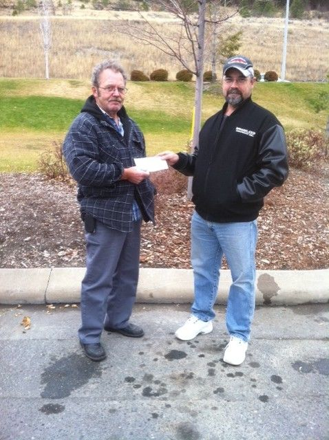 Alex Fraser (left), receives a cheque from NATG founder Larry Hall.