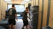 Movers with Two Men and a Truck secure a load of household goods.