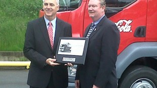 At left, Gary Moore, Kenworth general manager and Paccar vice-president, presents a  plaque and the keys to Kenworth's first K370 cabover to Coca-Cola Refreshments' Bob Slack, vice-president of field operations for the Pacific Northwest Marketing Unit.