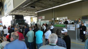 Potential buyers gather around to bid on an International tractor.