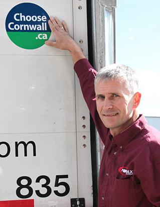 "Minimax Express Transportation president Yves Poirier poses with the new ""ChooseCornwall.ca"" decal on the back of one of his company's trailers. Minimax is one of several trucking companies in the area taking part in the initiative, which promotes Cornwall, Ont. as a place to do business."