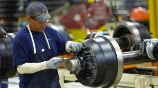 A plant employee assembles a trailer axle.
