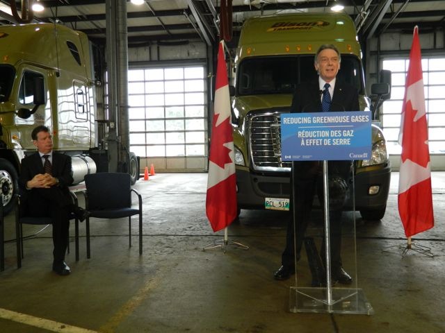 CTA's David Bradley looks on as Environment Minister Peter Kent announces Canada will follow the US lead when it comes to adopting GHG standards for heavy trucks.