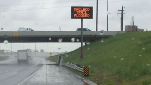 A sign warns that MacLeod Trail is flooded.