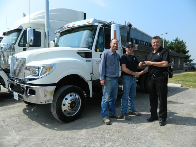 Tallman Truck Centre's Harvey Butcher (right) hands the keys to the company's first TerraStar 4x4 to Schindler Elevator driver Adam Maisonneuve, while Schindler's field supervisor Jeff Couch looks on.