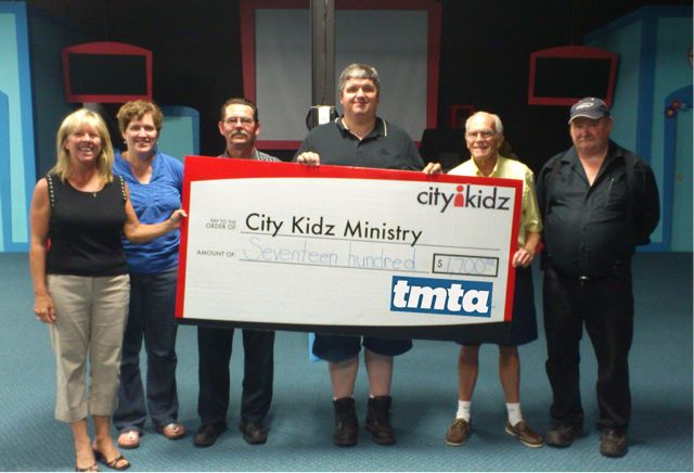 Steve Granville, Fred Pedler, Bob Dawson and Paul Crossman present a big $,1700 cheque to the funding team from City Kidz.