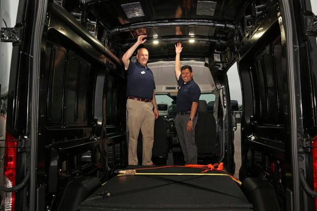 "Ford officials show off the interior height of the high-roof van. Derek Bier, on the left, is 6'6"". Photo by David Freers/Ford Motor Company."