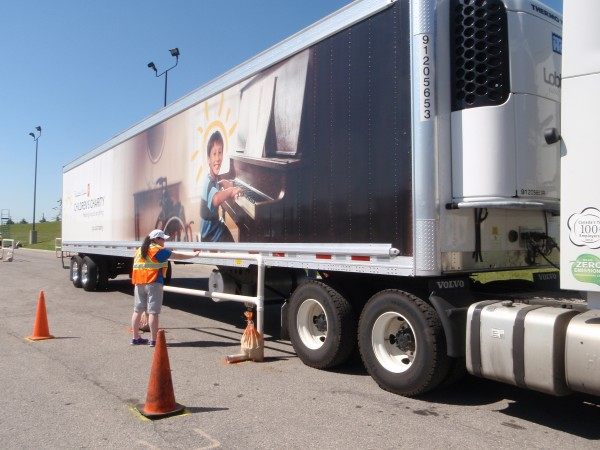 A judge examines a tractor-trailer participating in the Loblaw truck driving championships.