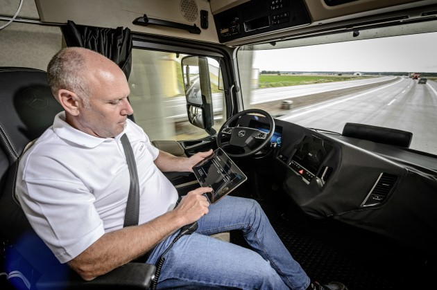 A driver performs other duties while Daimler's autonomous truck guides him down the road.