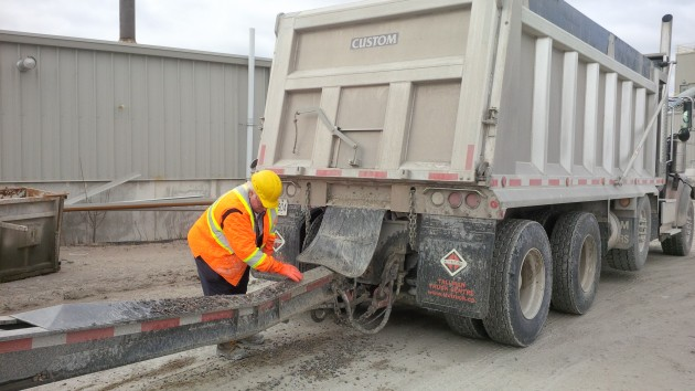 A true professional, driver Wayne Gary cleans off debris before leaving the concrete plant.