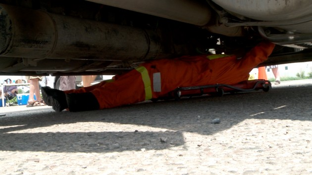 An MTO enforcement officer slides underneath a tractor-trailer during an inspection.