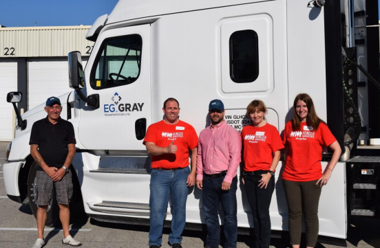 EG Gray owner Rob Tanguay (pink shirt) and EG Gray driver Jim Burgess (left) with Food Banks Canada volunteers prepare to deliver fresh food to communities across southern Ontario.