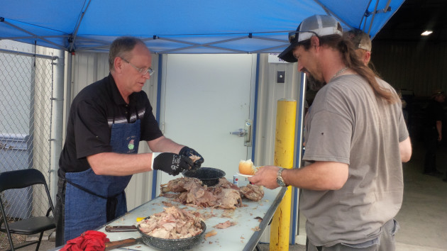 Doug Vandenberg serves a customer at Trison Tarps' third annual pig roast.