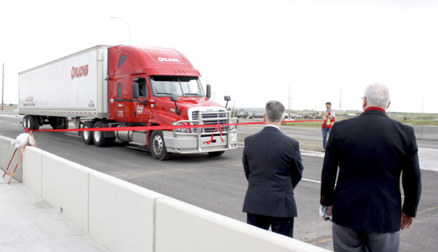 An Orlicks Inc. truck drives through the ribbon at the 61st Ave. S.E. extension opening June 23, as Gene Orlick and Mac Logan look on.