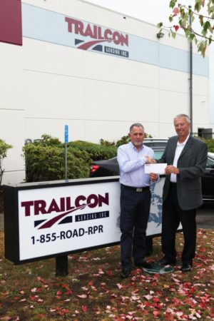 Randy Drake, left, of Stewart Trailers, and Alan Boughton of Trailcon Leasing commemorate the first days of Stewart Trailers operating as Trailcon.