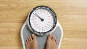 Female standing on bathroom scales. Copy space on a wooden floor.