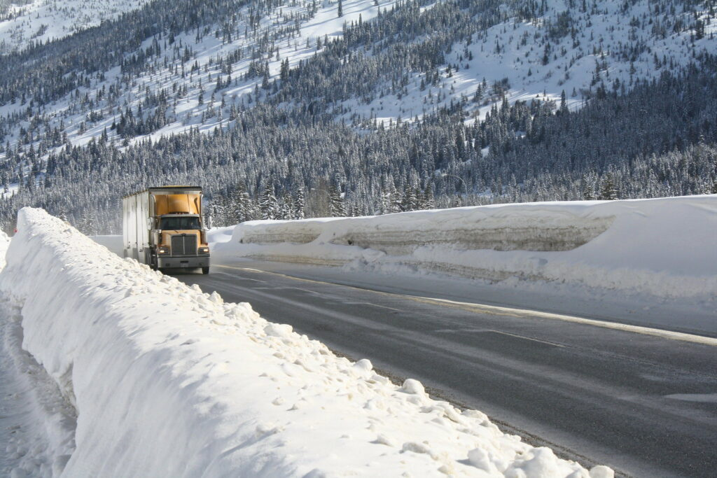 A truck driving driving through the mountains in winter.