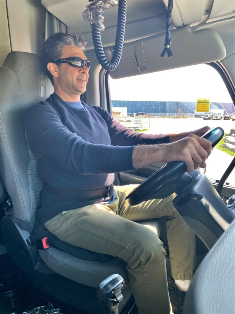 Longhaul driver Sameer Vij wears a posture-correcting device and sometimes places a rolled-up sweatshirt under his right thigh while working to help reduce pain and discomfort. (Photo: Leo Barros)