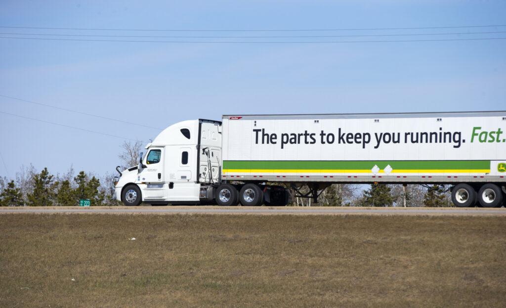 A John Deere truck hauling cargo along a highway. Taken in Edmonton, Alberta