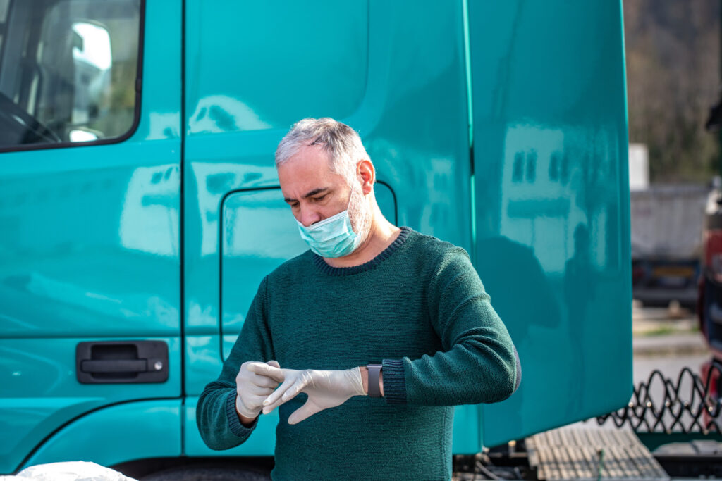 Truck driver with white gloves and face mask
