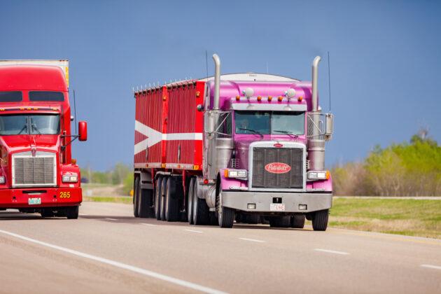 Two semi trucks drive on Highway 16 (Yellowhead Highway) between Lloydminster and Battleford, Saskatchewan, Canada on a cloudy day.