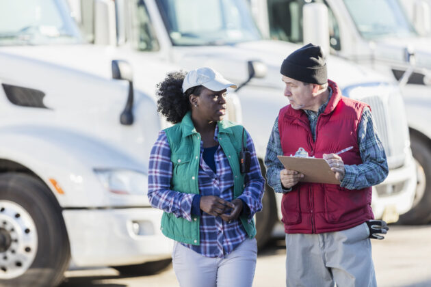 Two multi-ethnic truck drivers, a senior Hispanic man in his 60s and a mid-adult African-American woman in her 30s, standing in front of a fleet of semi-trucks or tractor-trailers. The man is holding a clipboard and they are conversing, looking at each other face to face.